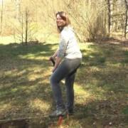 Susanne Schmidt tritt auf einer Waldlichtung einen Spaten in den Boden