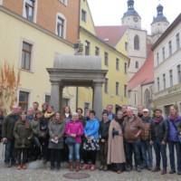 Gruppe vor historischem Brunnen und Altstadt