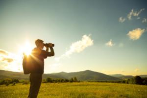 Junger Mann mit Fernglas auf Wiese vor Bergen