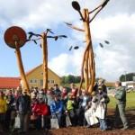Gruppe vor viele Meter hohem Kunstwerk aus Baumstämmen