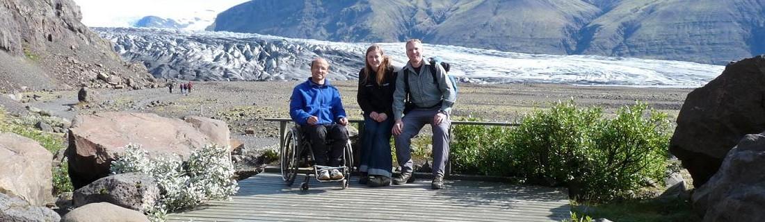 Freiwillige auf Bohlensteg in isländischer Berglandschaft