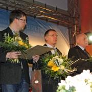 Drei Männer mit Blumensträußen auf einer Bühne