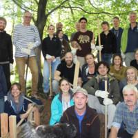 Eine Gruppe Erwachsener mit Arbeitshandschuhen, Holzpfählen und großen Hammern sitzt und steht an einem Hang im Wald.