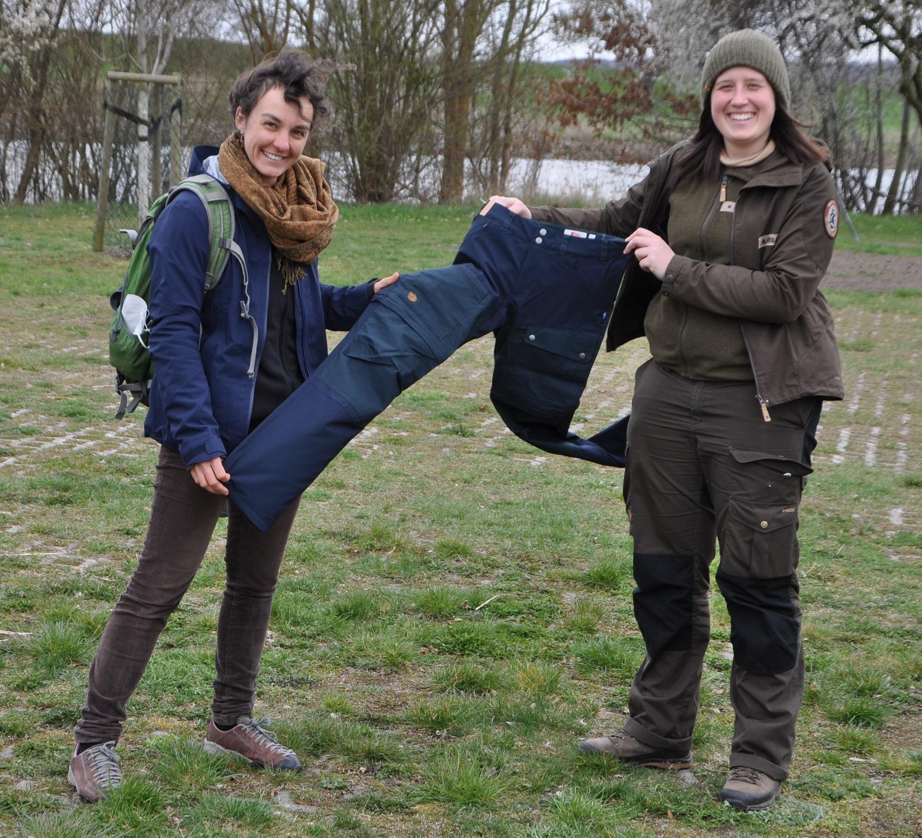 Zwei Frauen stehen auf einer Wiese mit Fluss im Hintergrund und halten zwischen sich eine blaue Hose.